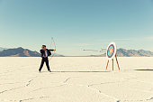 Young Boy Businessman Shoots Arrows at Target