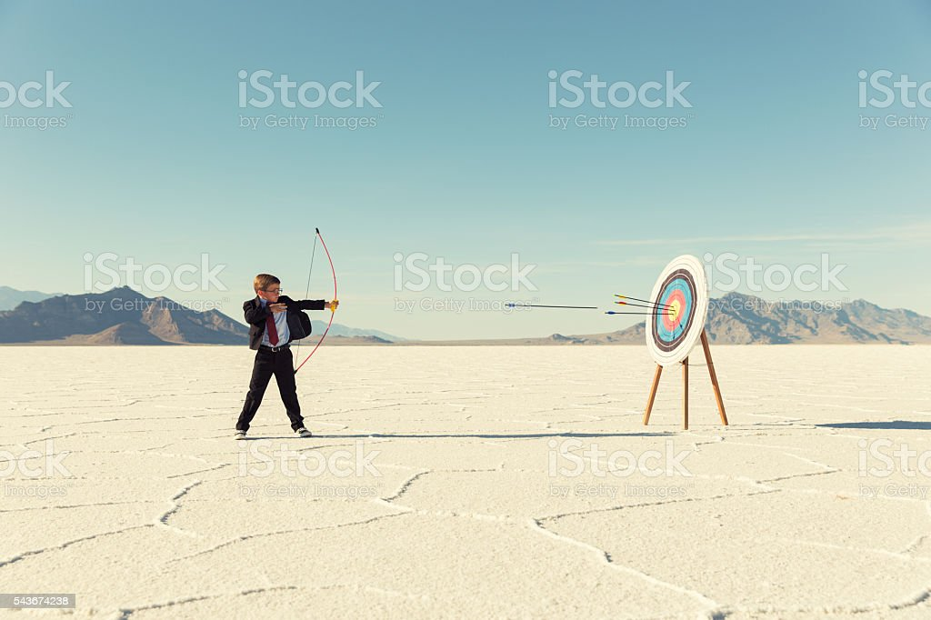 Young Boy Businessman Shoots Arrows at Target stock photo