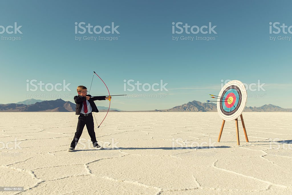 Young Boy Businessman Shoots Arrows at Target​​​ foto