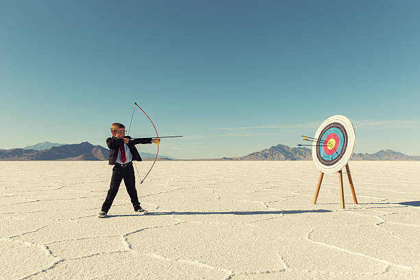 young boy businessman shoots arrows at target - sports target stock photos and pictures