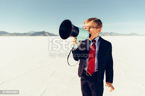 A young businessman shouts through a megaphone on the Bonneville Salt Flats in Utah, USA searching for new business opportunities. He is dressed in a suit and red tie with glasses. Retro styling.