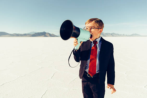 Young Boy Businessman Shouts Through Megaphone stock photo