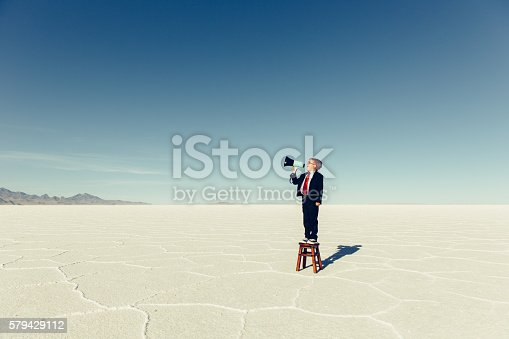 istock Young Boy Businessman Shouts Through Megaphone 579429112