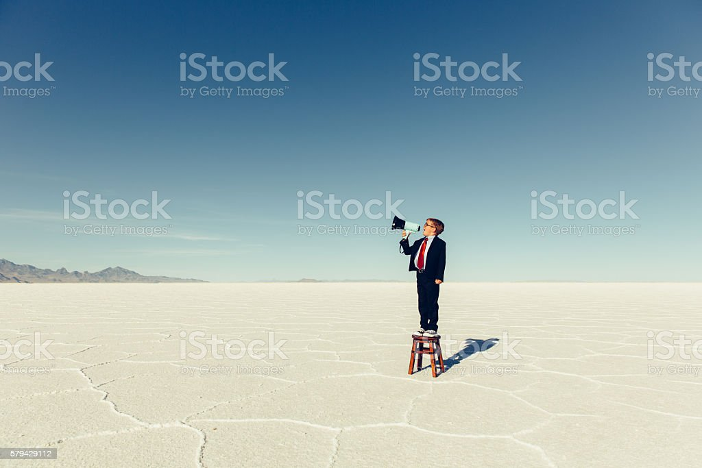 Young Boy Businessman Shouts Through Megaphone stock photo