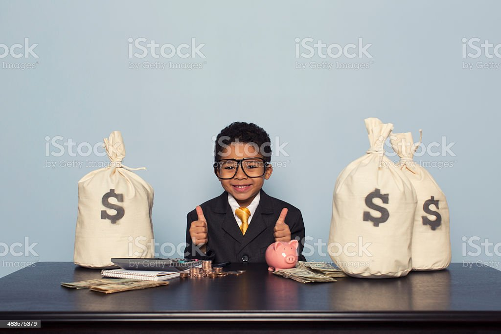 Young Boy Businessman Sits with U.S. Money Savings stock photo