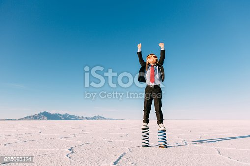 A young business boy dressed in business suit, flight cap and goggles stands on springs in the Utah desert. He is raising his arms to the sky imagining jumping and flying his business into the sky. Taken at the Bonneville Salt Flats in Utah, USA.