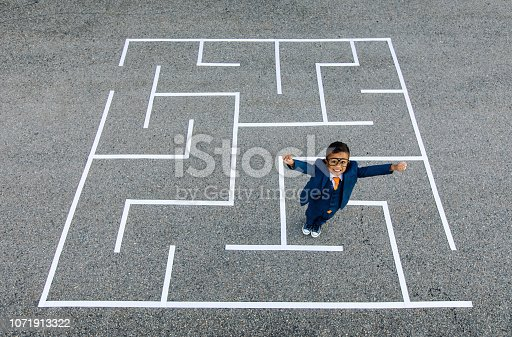 istock Young Boy Businessman Stands in Maze. 1071913322