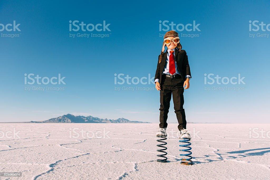 Young Boy Businessman Stands on Giant Springs stock photo