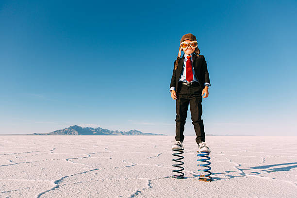 young boy businessman stands on giant springs - molla foto e immagini stock