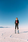 A young business boy dressed in business suit, flight cap and goggles stands on springs in the Utah desert. He is imagining jumping and springing his business into the sky. Taken at the Bonneville Salt Flats in Utah, USA.