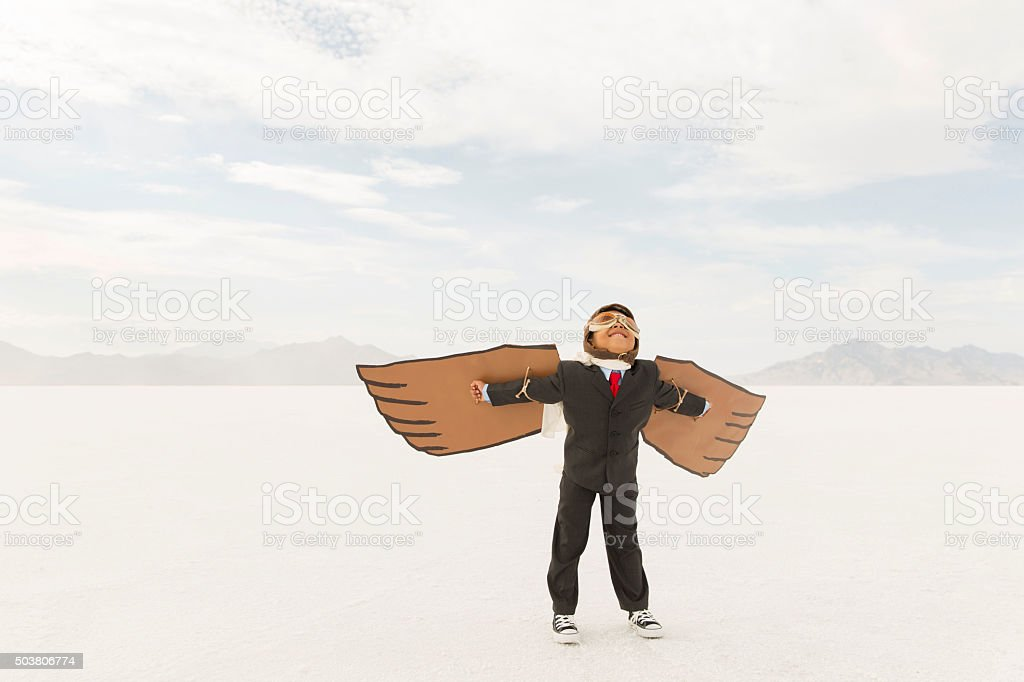 Young Boy Businessman Wearing Cardboard Wings stock photo