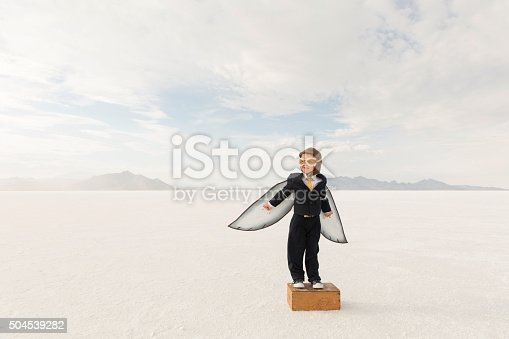 A young business boy dressed in business suit wearing cardboard wings and aviator goggles is ready to fly his business into the sky. He is standing on s box at the Bonneville Salt Flats in Utah, USA.