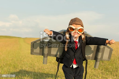 A young British boy is wearing a jetpack standing in a grass field located in the United Kingdom and is ready to take his business into the stratosphere.