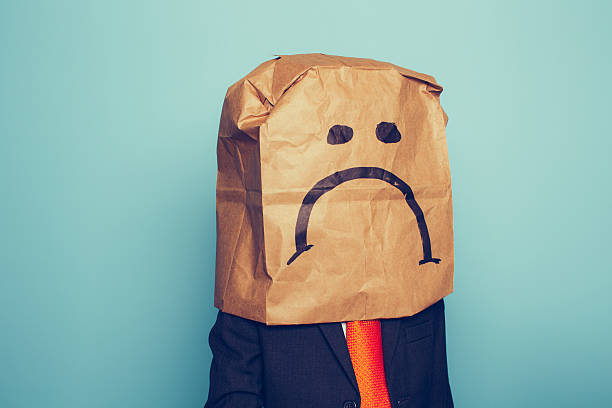 Young Boy Businessman Wears Sad Face A young boy dressed as a businessman wears a paper bag with a sad face on it The economy has pushed his business down. He sits at his desk with retro computer and phone. negative emotion stock pictures, royalty-free photos & images