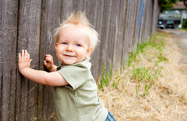 Young Boy by Fence stock photo