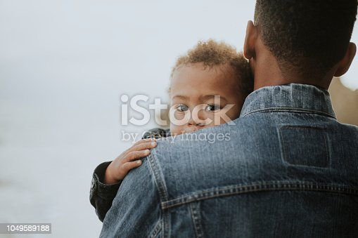 Young boy carried by his dad outdoors