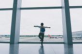 Young boy cheering at airport.