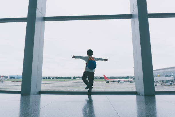 Young boy cheering at airport stock photo