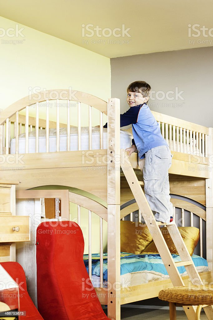 Young boy climbing ladder on wooden bunk bed in child's room stock photo