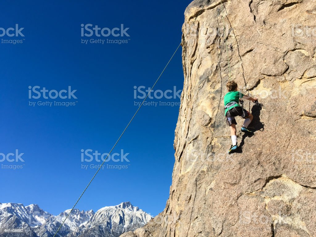Young boy climbing on the face of a rock in the mountains stock photo