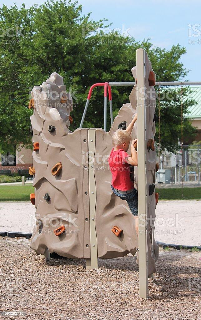 Young Boy Climbing Rock Wall Стоковые фото Стоковая фотография