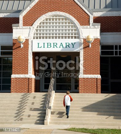 Young boy walks up steps to library entrance.