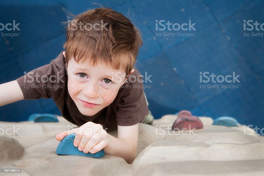 Young boy climbing up a wall at the playground stock photo