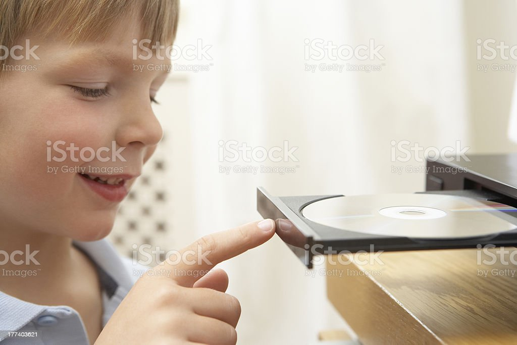 Young Boy Closing DVD Player With Finger stock photo