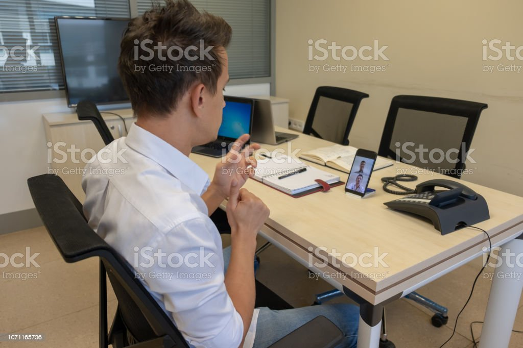 Young boy communicating with sign language at smart phone at office