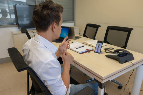 young boy communicating with sign language  at smart phone at office - sordità foto e immagini stock