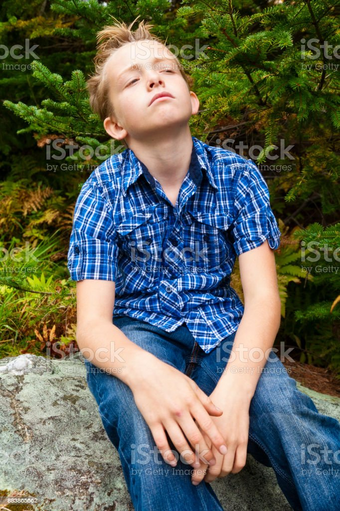 Young boy contemplates while sitting in the woods stock photo