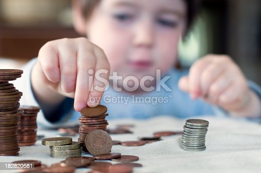 A three year old child stacks pennies. Narrow depth of field. UK
