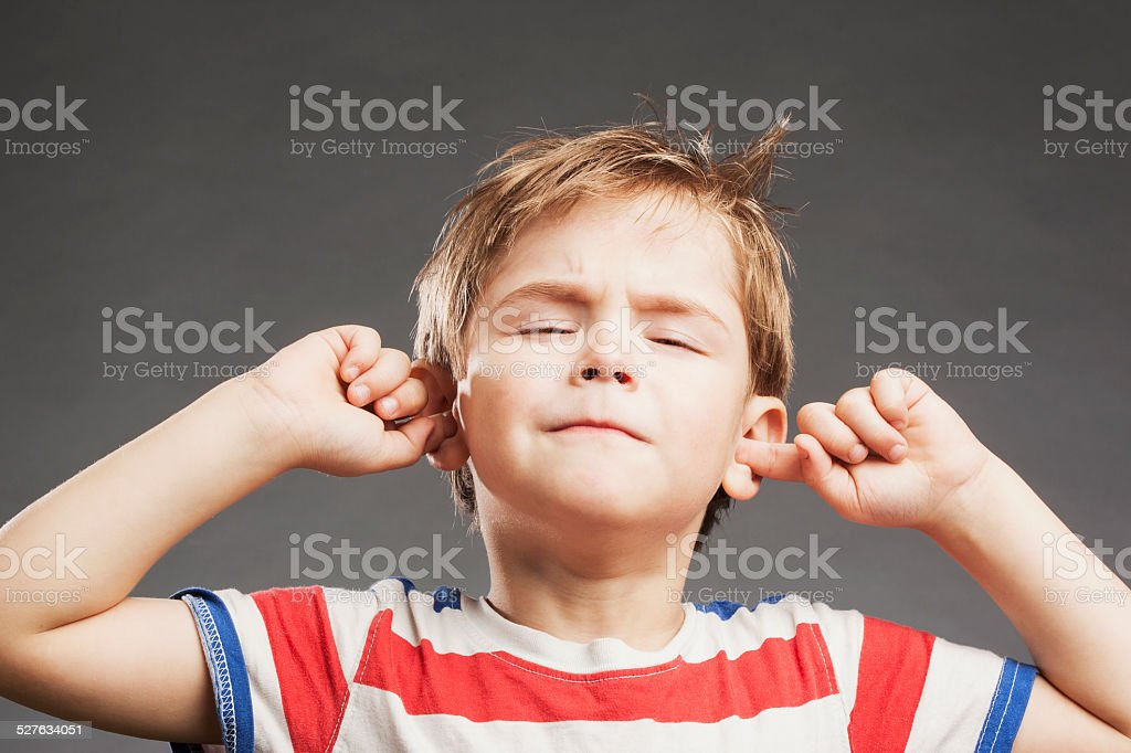 Young boy covering ears against gray background stock photo