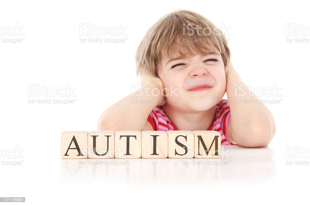 Young boy covering his ears with blocks spelling autism stock photo