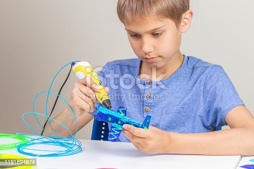 899701486 istock photo Young boy creating with 3d pen new object 1191894674