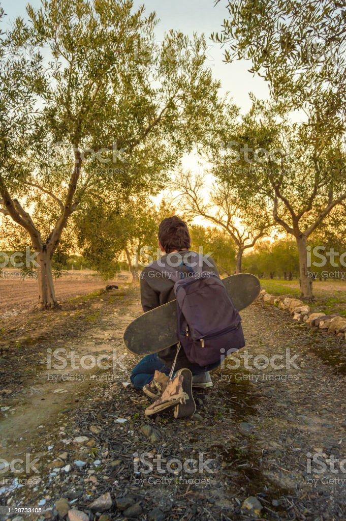Muchacho agachado y viajando por un camino rural con un monopatín y un colgante de zapatillas de su mochila. Chico descansando y mirando la puesta del sol. - foto de stock