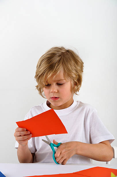 young boy cuts red colored paper stock photo