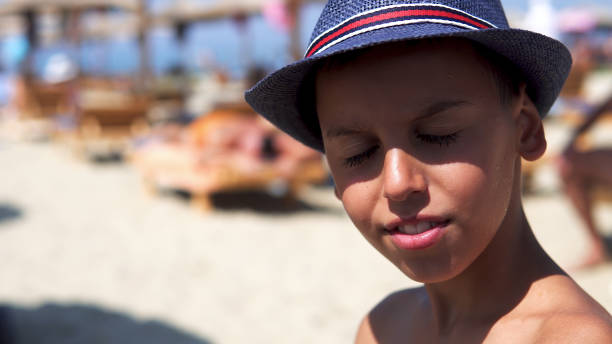 Young boy dazzled by summer sun on beach put on protection hat and smile to camera Young boy dazzled by summer sun on beach put on protection hat and smile to camera dazzled stock pictures, royalty-free photos & images