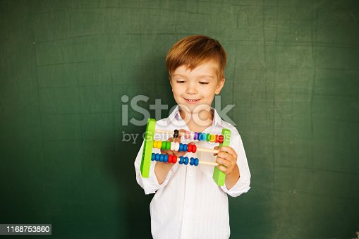 istock Young boy described at the green blackboard at school thinking about the task. Back to school concept. 1168753860