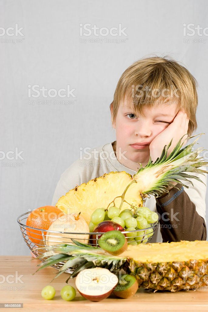 young boy doesn't want to eat healthy fruit royalty-free stock photo