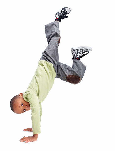 Young boy doing a handstand against white stock photo
