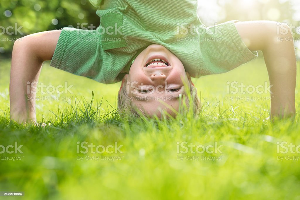 Young boy doing a headstand on the grass - foto de stock