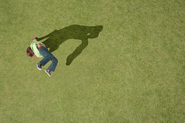 Young boy doing cartwheel in grass stock photo