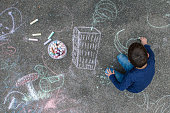 Young boy drawing outside on the sidewalk with chalk.