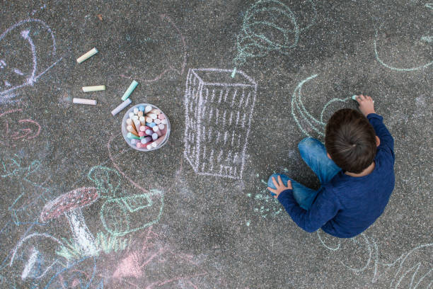 Young boy drawing on the sidewalk with chalk Young boy drawing outside on the sidewalk with chalk. chalk art equipment stock pictures, royalty-free photos & images