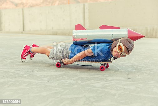 A young boy is lying on a skateboard, in an urban environment with a homemade rocket strapped to his back. He loves science and technology and wants to zoom along in a rocket when he grows up.