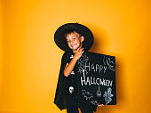 young boy dressed as a magician is holding happy halloween chalkboard in front of orange background