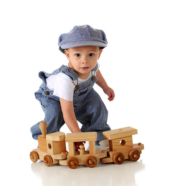Young boy dressed as a train conductor A todder in striped denim overalls and engineer's cap playing with a wooden train.  Isolated on white. bib overalls boy stock pictures, royalty-free photos & images