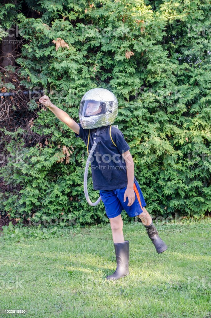 Young boy dressed as an astronaut in the backyard during summer day