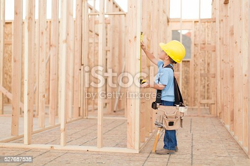 527687520 istock photo Young Boy dressed as Carpenter with Tape Measure 527687538